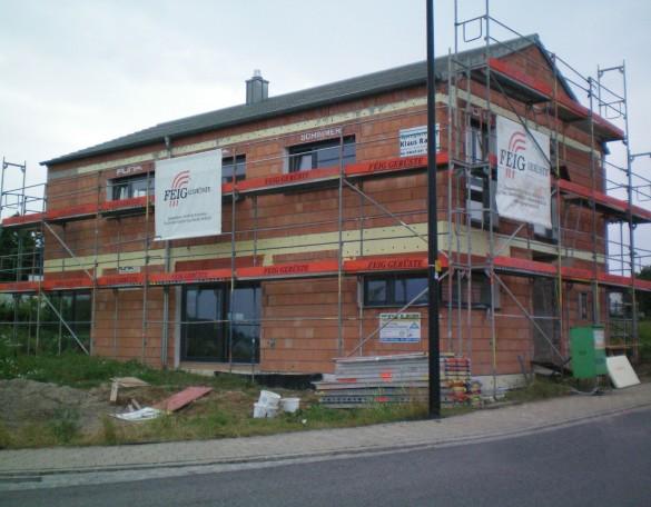 Ein Fassadengeruest der FEIG-Gerueste-GmbH an einem Bauplatz.