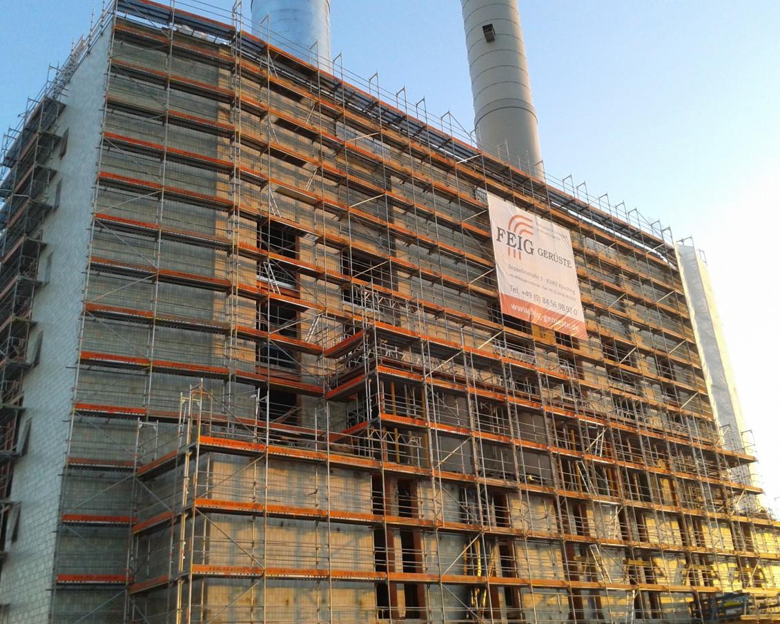 Geruestbau-Arbeiten am Olympiatower in Muenchen bei Sonnenaufgang.